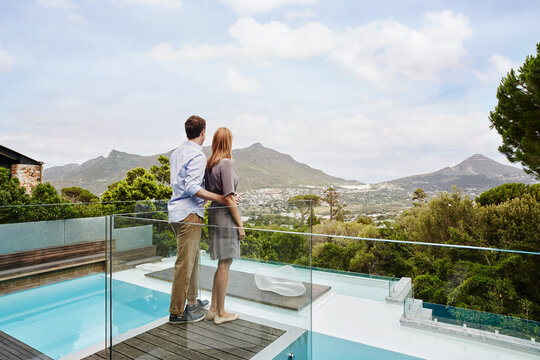 Heterosexual couple standing while looking at view from balcony of modern house