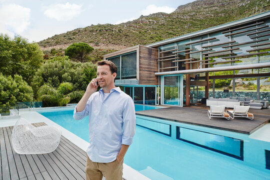 Mature man talking on phone with hands in pockets standing against modern house