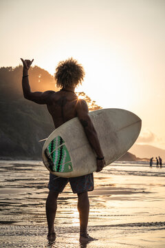 Man gesturing while standing with surfboard at seashore during sunset
