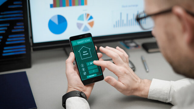 Smart home, application on the phone. A man manages various parameters of his home from a smartphone. Smart home technologies allow you to control lighting, temperature, security systems
