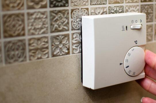 Closeup of hand using floor temperature controller at home