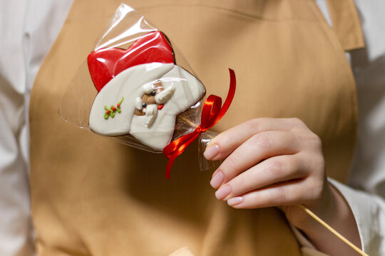 A pastry chef is holding a gingerbread in the shape of Santa Claus. The symbol of the new year and merry christmas.