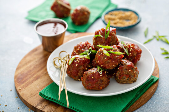 Asian meatballs appetizers with sweet and sour sauce and wooden skewers