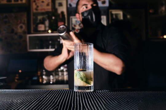 Male bartender with mask making drinks.