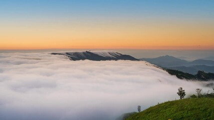 Wall Mural - Time lapse of foggy moving over mountains at sunrise.