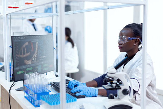 African chemist researcher typing information on computer from experimental drug trial. Black healthcare scientist in biochemistry laboratory wearing sterile equipment.