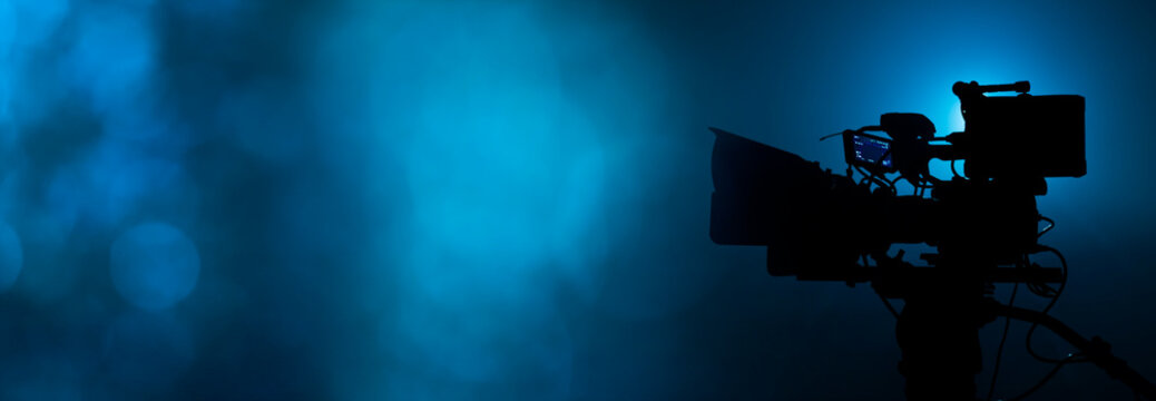video camera silhouette in the dark banner with blue light and bokeh, movie or television broadcasting background with copy space