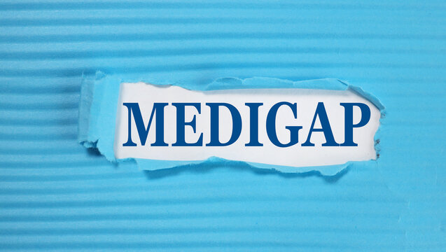 MEDIGAP. text on white paper on torn blue paper background