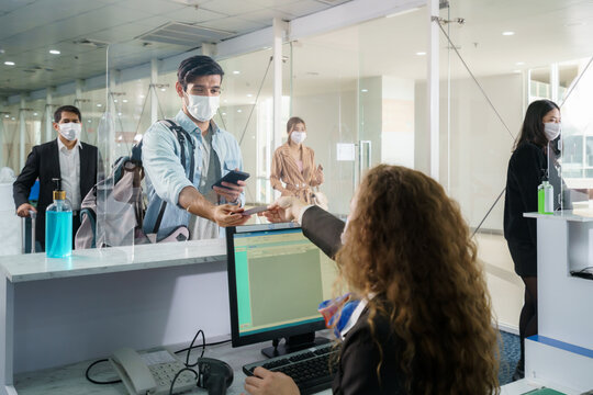 A male airline passenger with mask is handing over his passport at the airline counter check in through an acrylic barrier for disease prevention coronavirus or covid-19