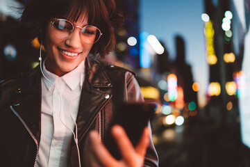 Smiling hipster girl in eyewear reading message with good news from friend holding mobile smiling at night city street, pretty woman in headphones enjoying downloaded new song via application on phone