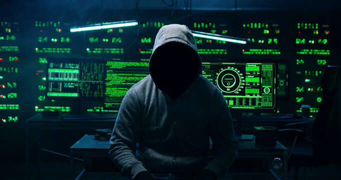 Portrait of  incognito hacker using computer for organizing massive data breach attack on corporate servers. Secret location surrounded by displays, servers and cables.