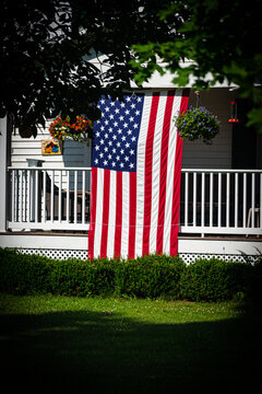 An American flag is hung on the front porch of this home in the small town of Windsor in Broome County in Upstate NY.  Proud to fly the Stars and Stripes for all Patriots to see.