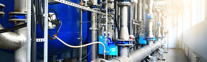 Large industrial water treatment and boiler room. Shiny steel metal pipes, blue pumps, valves. Industry, technology, special equipment, biotechnology, chemistry, ecology, heating. Panoramic image