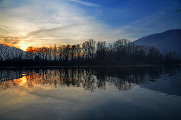 Beautiful sunset scenery over the lake with silhouettes of trees reflected in the water