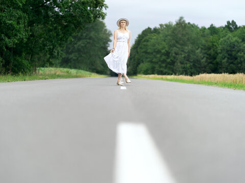 A woman in a white dress stands on the road. Travel concept, the beginning of the journey.