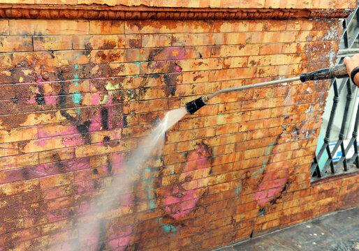 Trabajador limpiando grafitis de una fachada