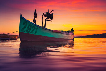 2021 concept. Fishing boat on shore and ripple sea water on dramatic colorful sunset