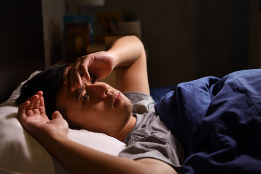 A depressed young man suffering from insomnia lying in bed..
