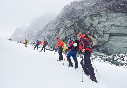 Side view of hikers team standing on snowy hill near huge rocky mountains. Male mountaineers with backpacks and trekking sticks wearing hiking sunglasses and winter jackets. Concept of alpinism
