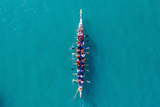 Dragon Boat team rowing to the pace of an onboard Drummer, Aerial view.