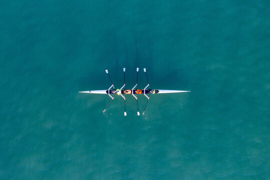 Sport Canoe with a team of four people rowing on tranquil water, Aerial view.