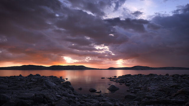 Dramatic lake scene at sunset with a stormy sky and a warm golden glow on the horizon. A calm, tranquil and serene, natural landscape.