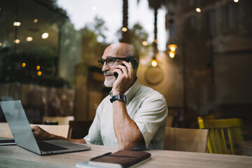 Obraz Elderly male freelancer on retirement sitting at coworking desktop with modern netbook technology for doing distance job and making consultancy smartphone talking, aged man in eyewear caling - fototapety do salonu