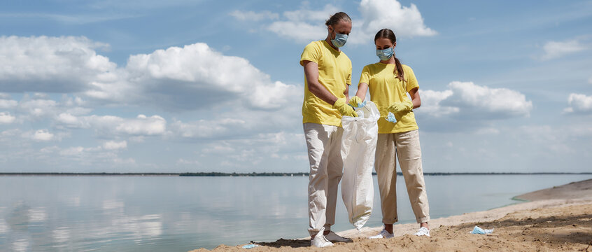 Coronavirus and the environment. Two young eco volunteers wearing uniform and rubber gloves collecting used medical face masks on the beach during covid pandemic