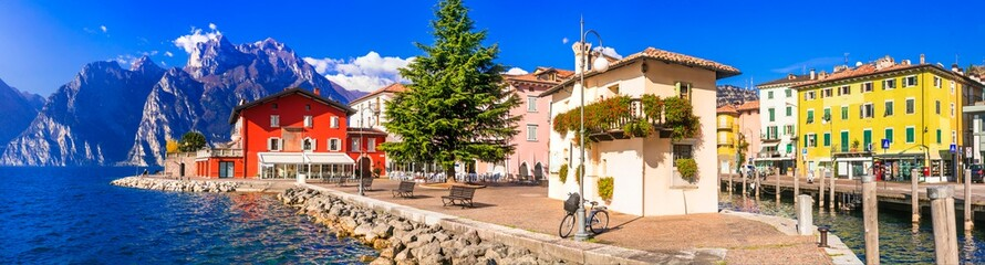 Beautiful lake Lago di Grada. Panoramic view of Torbole village with colorful houses . Italy