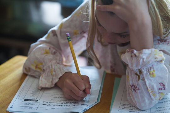 Child, holding a pencil, tries to concentrate on schoolwork at a desk.