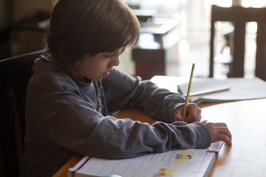 Young boy writes on his paper at a desk.