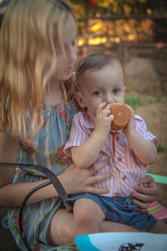 Little girl holds one yr old little boy as he eats a cupcake.