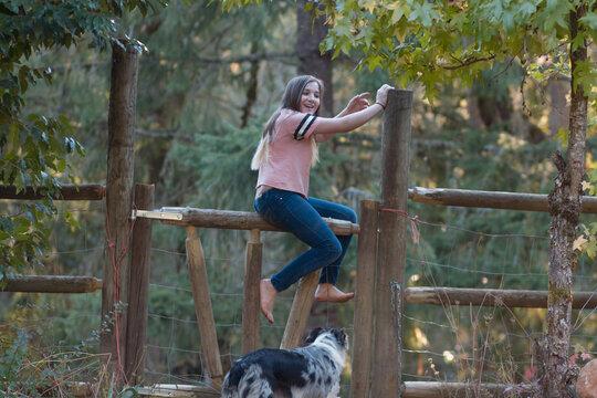 Teenage girl sits on a fence alongside her border collie dog.