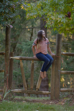 Teenage girl smiles as she sits on a pole fence near a forest.