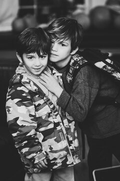 Boys embracing while looking at the camera.