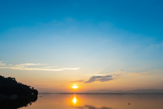Sunrise at reservoir with mountain blackground and blue sky in morning time. Nature park and outdoor background