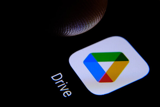 Stafford / United Kingdom - November 12 2020: Google Drive app and blurred finger tip above it ready to press the sreen of smartphone. The application