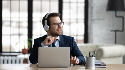Dreamy businessman wearing headphones using laptop, sitting at desk in office, looking to aside,...