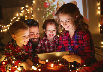 Merry Christmas! happy family  with glowing garland makes a video call on Christmas holiday in bed near tree at home .