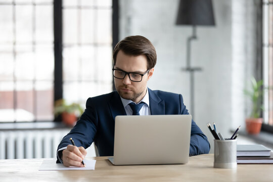 Confident businessman wearing suit and glasses using laptop, writing notes or financial report, sitting at desk in office, focused young entrepreneur working with documents or marketing plan