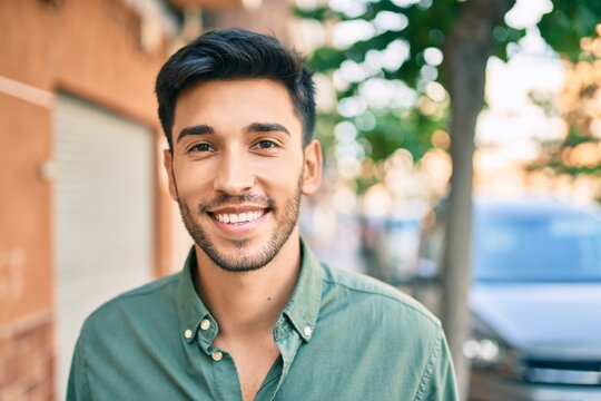 Young latin man smiling happy walking at the city.