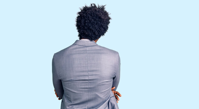 Handsome african american man with afro hair wearing business jacket standing backwards looking away with crossed arms