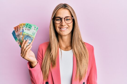 Young blonde woman wearing business style holding australian dollars looking positive and happy standing and smiling with a confident smile showing teeth