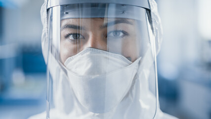 Dramatic Shot of Heroic and Overworked Medical Worker Wearing Coverall, Face Mask and Shield Looks...