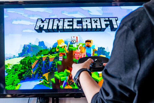 Woman holding a steam controller and playing popular video game minecraft on a television and PC