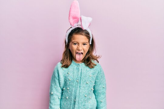 Little beautiful girl wearing cute easter bunny ears sticking tongue out happy with funny expression. emotion concept.