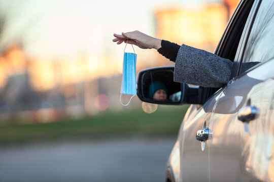 Female driver throws out a used facial mask through a car window or shares a new clear with somebody, copyspace