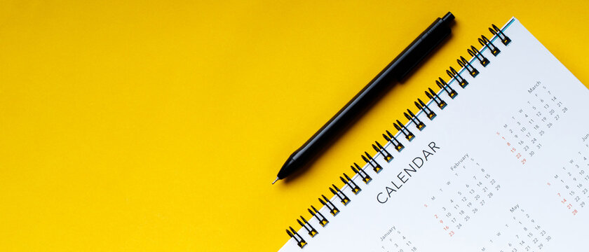 A pen with calendar on yellow background