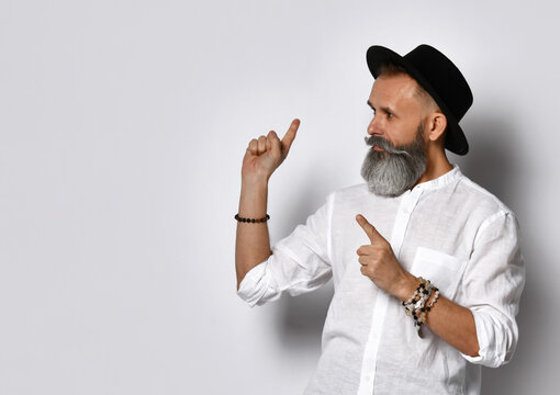 Portrait of a fashionable senior hipster with a handsome mustache and beard, wearing a black hat and white shirt. The person grabs your attention by pointing to something to the side of him.