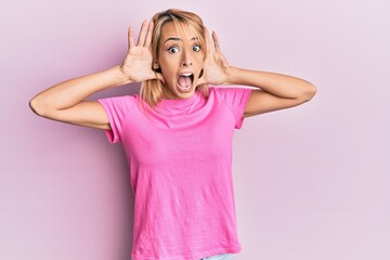 Beautiful blonde woman wearing casual pink tshirt smiling cheerful playing peek a boo with hands showing face. surprised and exited Wall mural